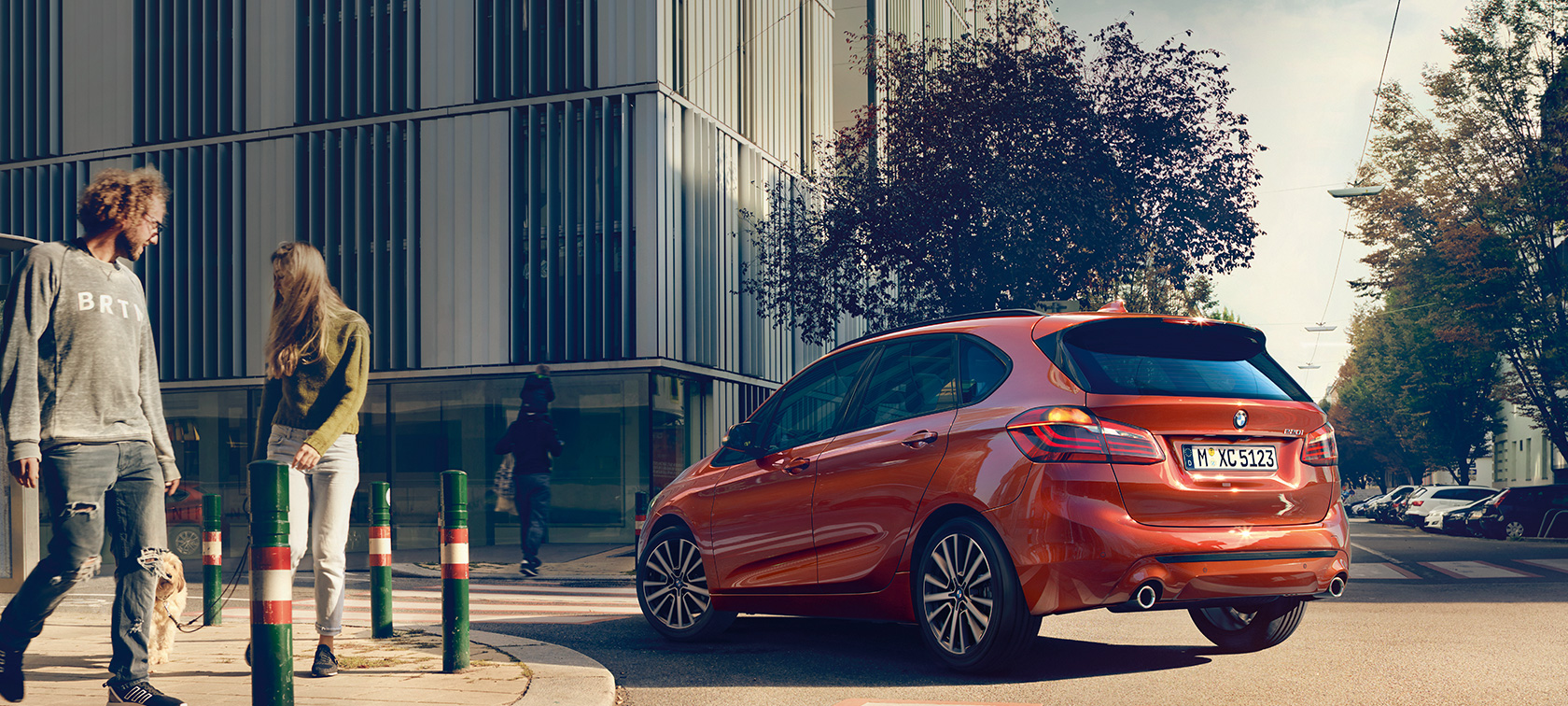 BMW 2 Series Active Tourer 220i F45 Sunset Orange metallic three-quarter rear view driving on the road