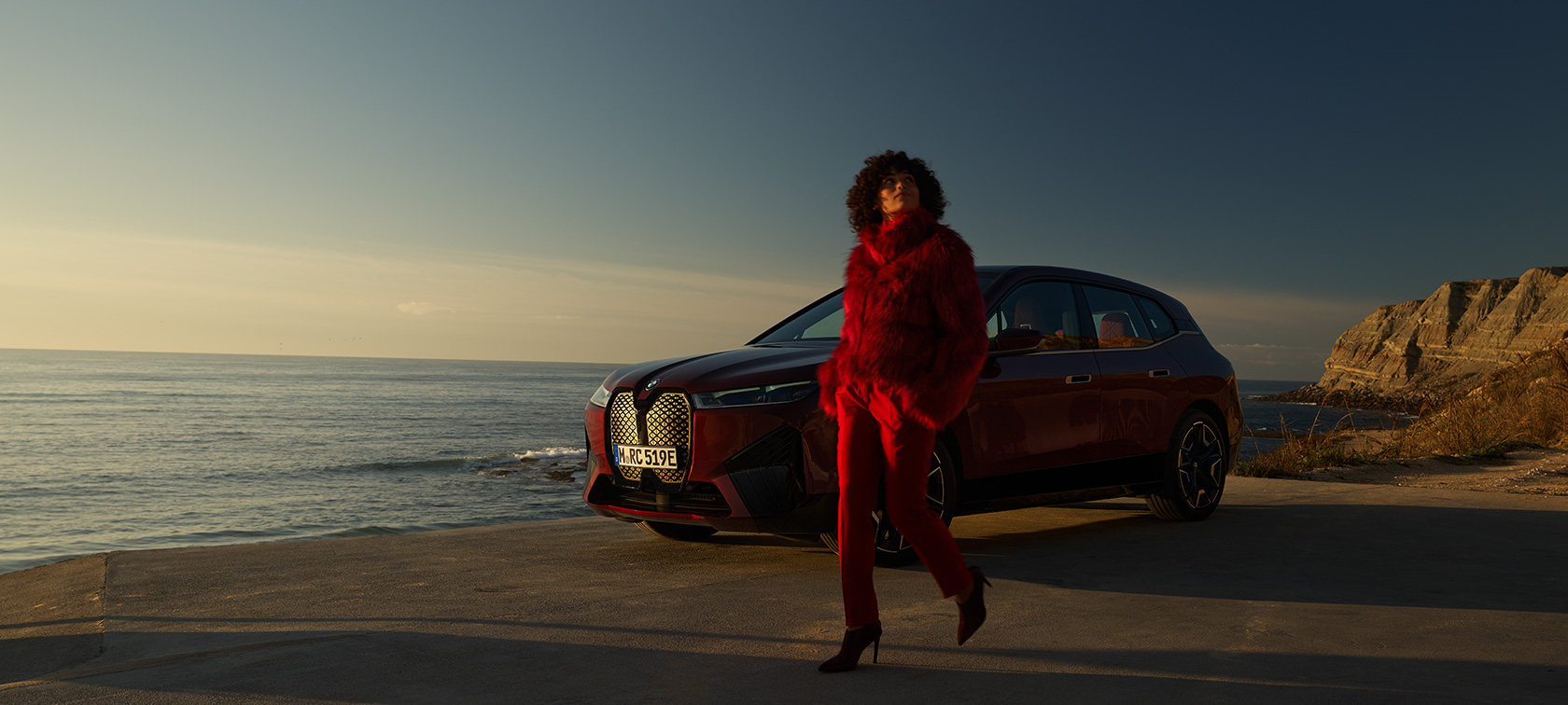 BMW iX Aventurin Red i20 three-quarter side view in front of the coast with model