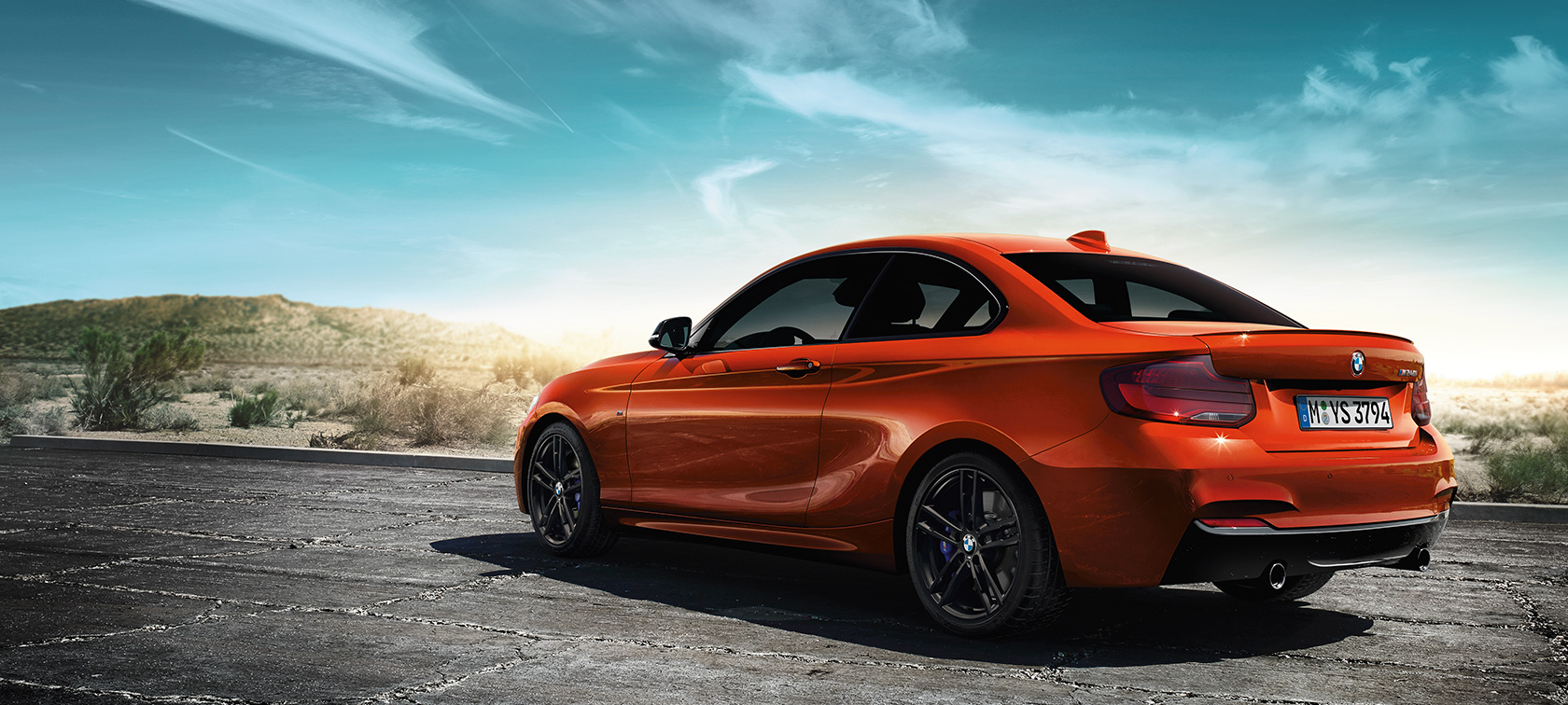 BMW M240i Coupé F22 2017 Sunset Orange metallic three-quarter rear view standing in front of steppe landscape