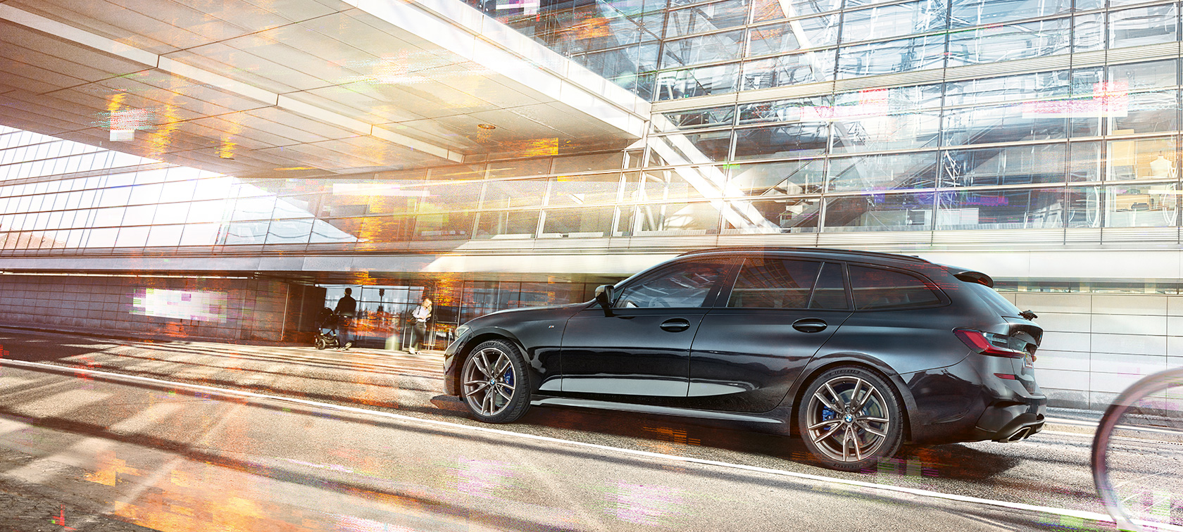 BMW M340i xDrive Touring, lateral driving shot in front of an urban glass building