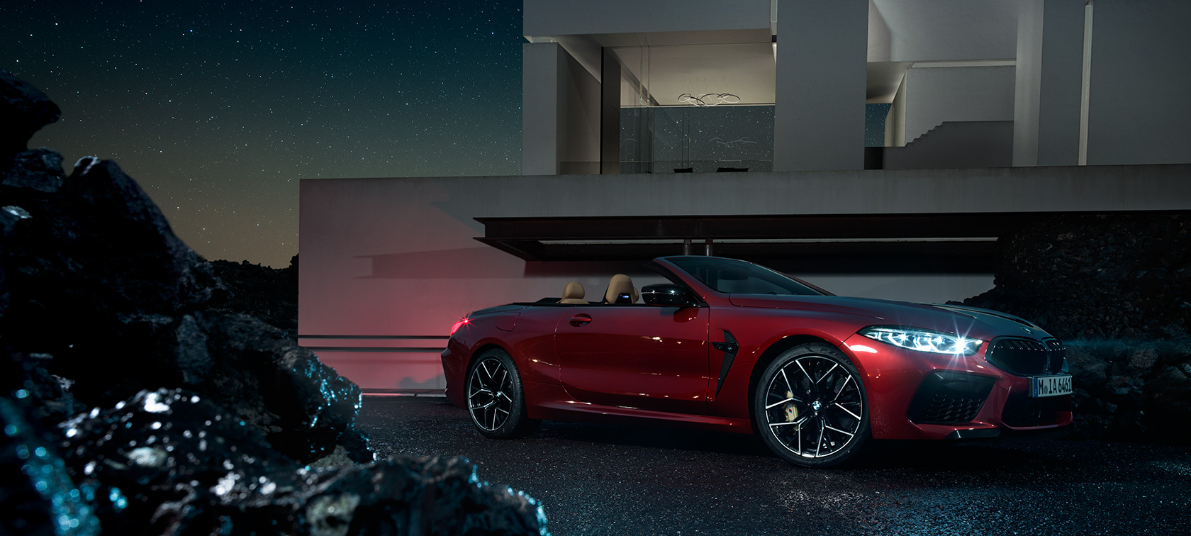 BMW M8 Competition Convertible in Motegi Red metallic, three-quarter side view, standing at night in front of villa.